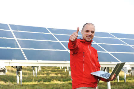 Male engineer using laptop, solar panels in background