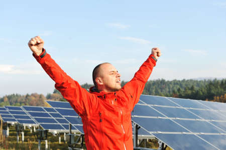 Success, engineer in solar panel fields with arms up photo