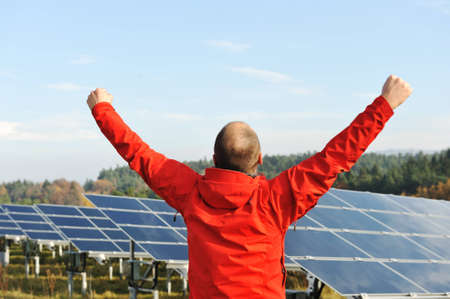 back up: Success, engineer in solar panel fields with arms up Stock Photo