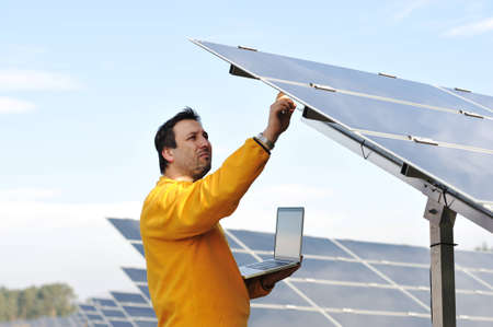 Young expert working at solar panels photo