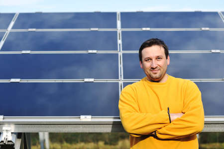 Young male engineer with solar panels in background photo