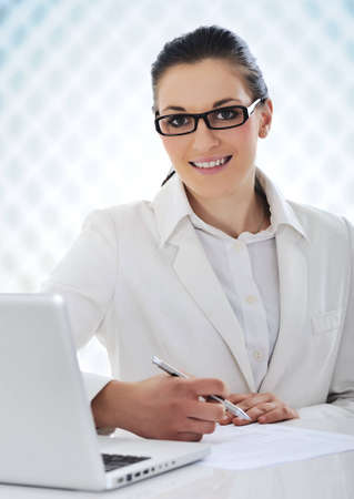 Confident business woman at desk in office with laptop and documents photo