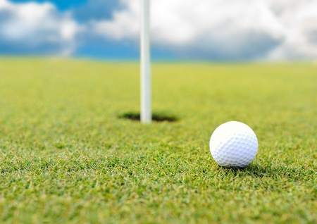 driving range: Golf ball at hole on grass field Stock Photo