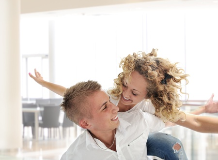 looking around: Portrait of a romantic young couple smiling together over white background Stock Photo