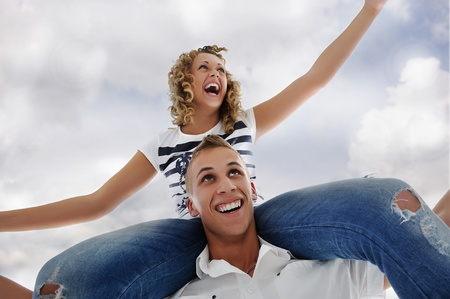 Portrait of teenage couple piggybacking isolated in white photo