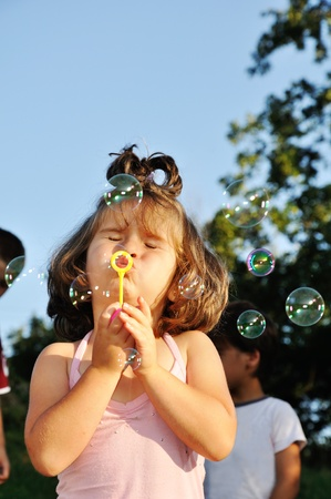 Little girl blowing soap bubbles photo