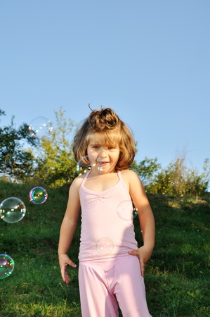 Little girl with soap bubbles looking at camera Stock Photo - 13375478