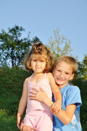 Two little girls standing together in the park, one holds another photo