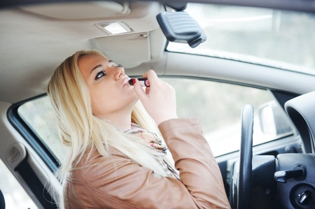 Girl putting on lipstick in car photo