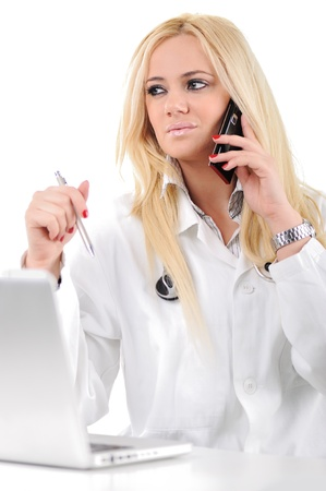 Portrait of a doctor doing her work with laptop and mobile phone photo