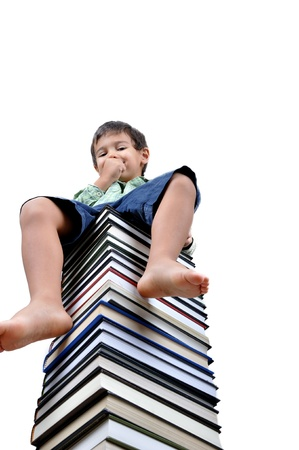 Little boy sitting on books isolated in white photo