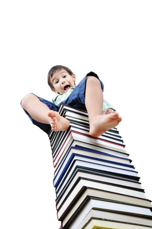 Cute little boy  sitting on heap of textbooks photo