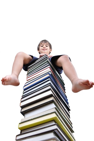 Little boy sitting on large stack of books photo
