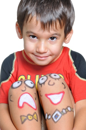 Cute little boy with painted smileys on his legs photo