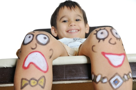 Little boy with painted smileys on his legs Stock Photo