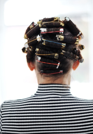 Woman with curlers on head, back Stock Photo