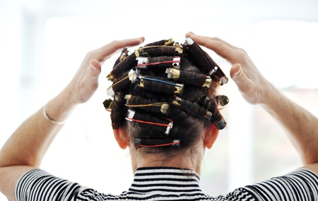 Woman with curlers on hair, back