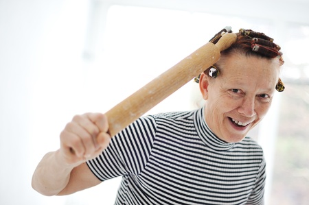 Senior woman with a rolling pin and curlers on hair photo