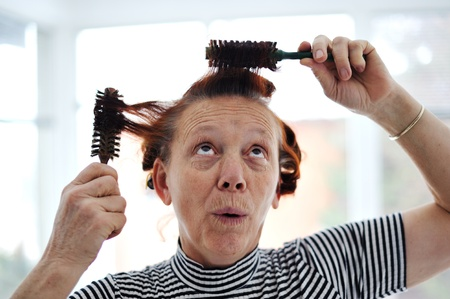 Senior lady hairdressing with many combs photo