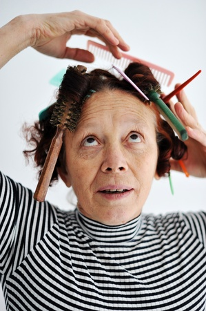 Senior female multitasking with many combs in hair photo