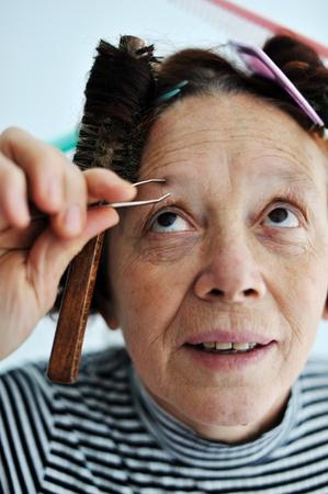 tweezing eyebrow: Senior woman tweezing eyebrow Stock Photo
