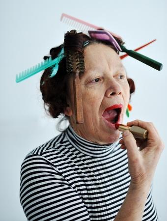 Senior woman putting lipstick photo