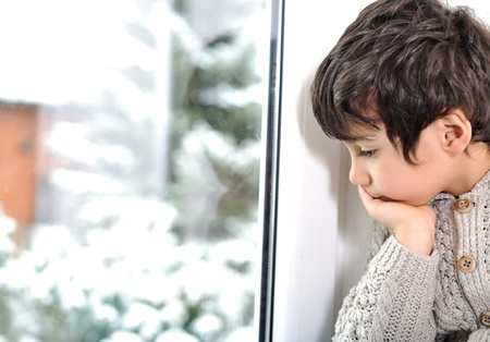 Sad kid on window cannot go out because of cold and snow Stock Photo