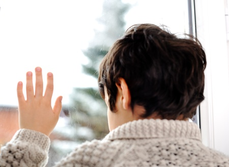 sadness: Sad kid on window and winter snow is outside Stock Photo