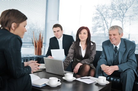 Businesswoman in an interview with three business people getting positive feedback photo