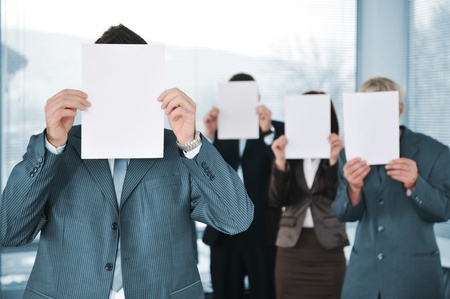 Business team of four holding blank paper photo