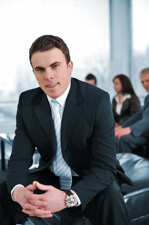 Businessman with his co-workers in office smiling, looking at camera photo