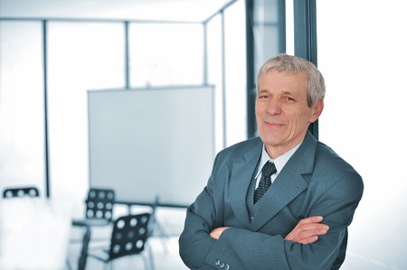 Businessman standing with folded arms photo