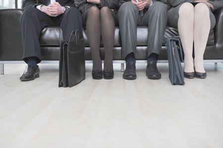 business woman legs: Business people sitting on couch
