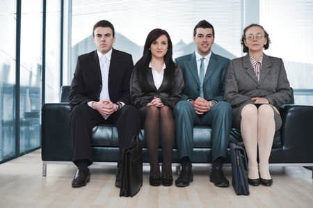 Four business people sitting in a row on sofa photo