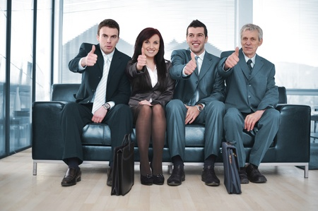 positivismo: Grupo de gente de negocios sentado en el sof� con el pulgar hacia arriba