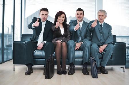 positivism: Gruppo di uomini d'affari seduto sul divano con i pollici in su