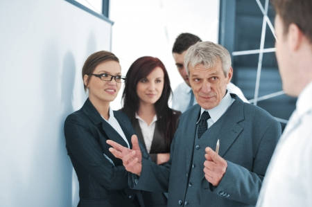 convince: Small business team in the office in front of a whiteboard discussing a project Stock Photo