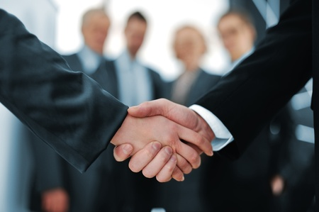 strong partnership: Handshake in front of business people Stock Photo