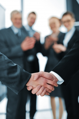 business handshake: Succesful handshake with business people aplauding