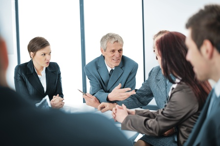 meeting room: Portrait of a positive manager with his team sitting at the table Stock Photo