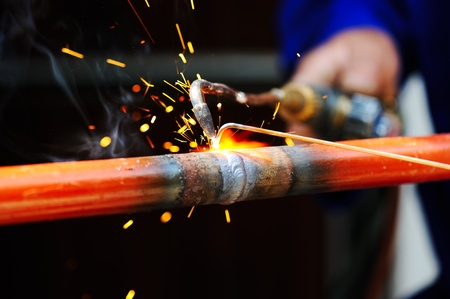 welding worker: welder using torch on metal object Stock Photo