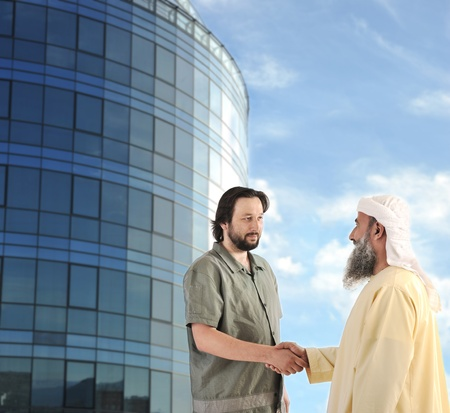 Arabic Muslim businessman meeting outdoors in front of modern building photo