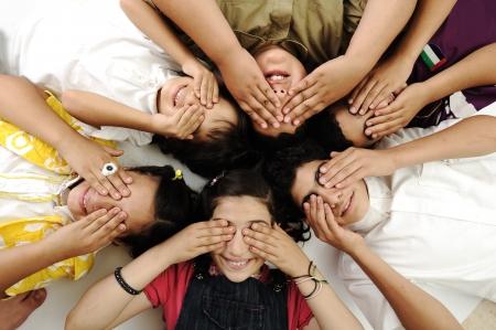 eyes closing: Ni�os felices que ponen en los ojos de cierre de tierra Foto de archivo