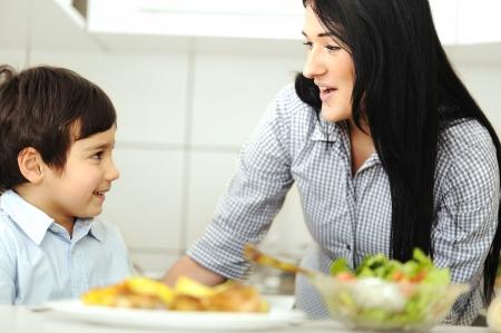 comida arabe: Ni�o peque�o en la cocina con la madre Foto de archivo