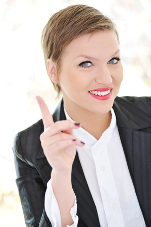 Portrait of young business woman pointing UP photo