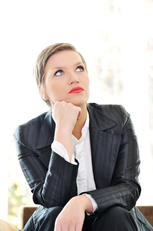Young business woman sitting at office and thinking photo