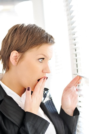 fear woman: Young woman with shocked expression looking trough window Stock Photo