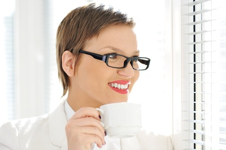 Young smiling business woman drinking coffee while looking outside through window photo