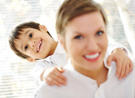 Portrait of young mother piggybacking her son indoor photo