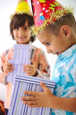 Cute kid receiving birthday present box photo
